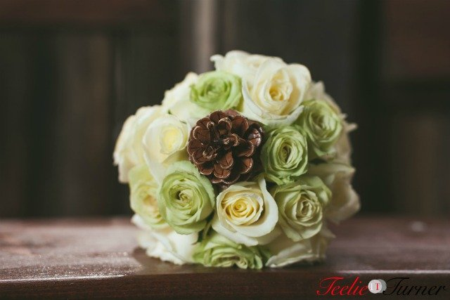 Arrangement of wedding bouquet with white and green roses.