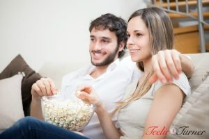 Young couple eating popcorn while watching a movie