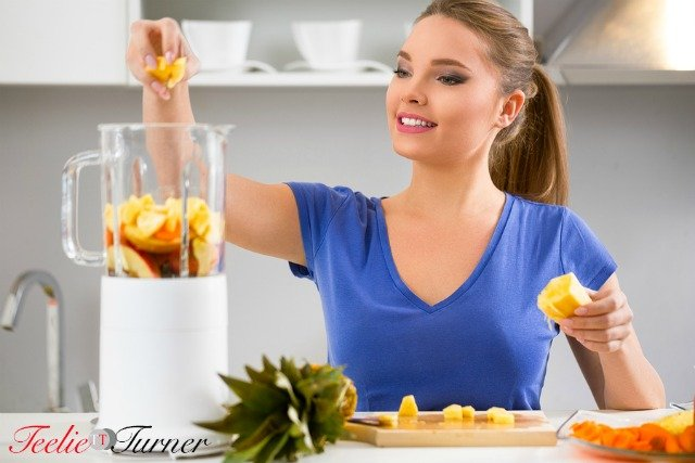 Juicing-woman making fruit juice using juicer machine at home in kitchen