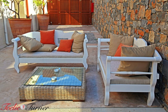 Beautiful mediterranean patio with white outdoor furniture,  pillows and table