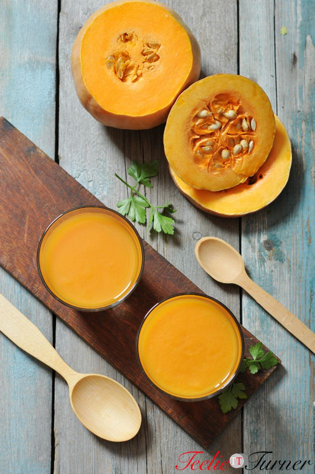 Pumpkin smoothie in glass on rustic wooden background